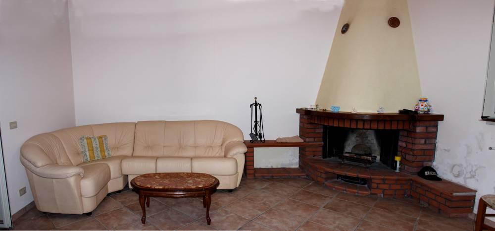 Divano e caminetto della villa in vendita nel Comune di Mirto